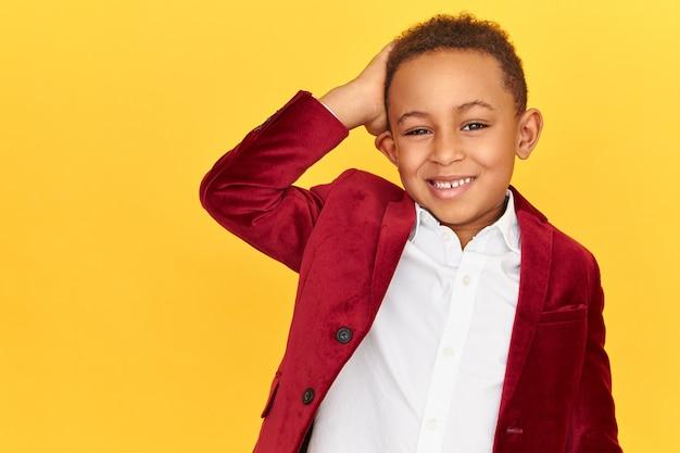 Immagine del ragazzino africano alla moda attraente che guarda l'obbiettivo con un ampio sorriso allegro, sentendosi a disagio, grattandosi la nuca, dimenticato il tuo compleanno, posando sul muro dello spazio Foto Gratuite