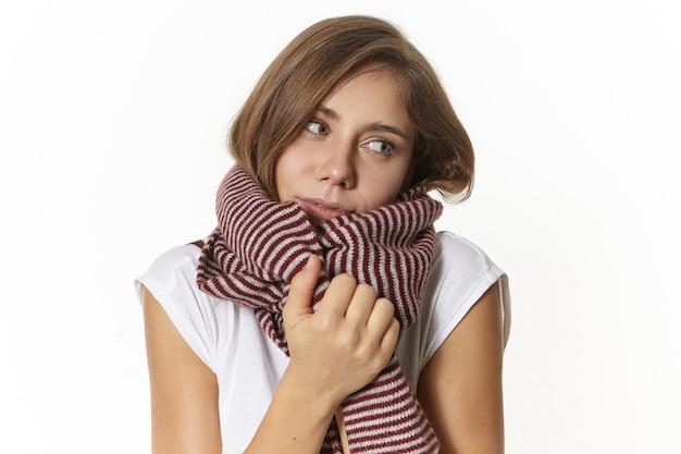 Foto di bella donna in maglietta bianca in fase di riscaldamento essendo avvolto in sciarpa di lana a righe Foto Gratuite