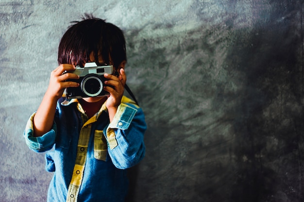 Picture of a boy holding a camera Premium Photo