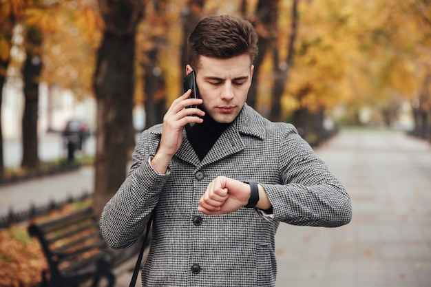 Picture of businesslike man speaking on mobile phone while going on meeting, checking time with watch on hand Free Photo
