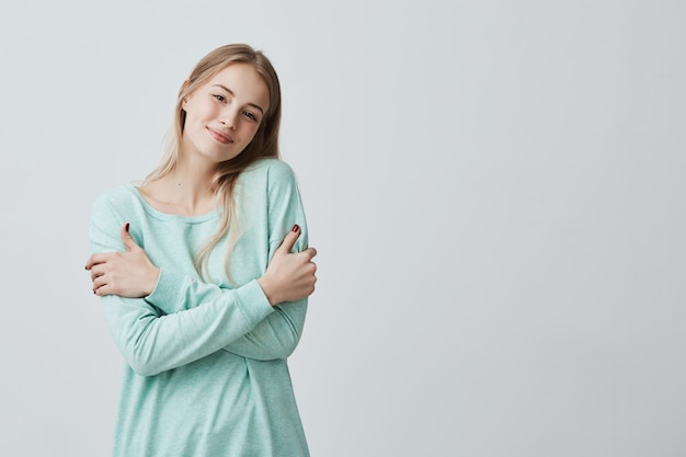 Picture of cheerful beautiful young european female dressed in blue sweater smiling happily, hugging herself, having positive joyful expression on her face. people, lifestyle and happiness Free Photo