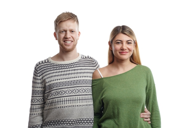 Foto di allegre giovani coppie europee in vestiti alla moda in posa con sorrisi felici: ragazzo barbuto in maglione che abbraccia la sua ragazza bionda dalla sua vita. persone, amore e relazioni Foto Gratuite