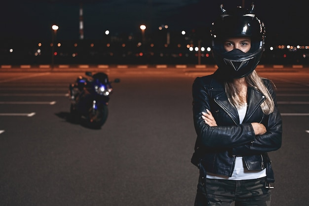 Picture of confident self determined young female rider in safety helmet standing in parking lot keeping arms crossed and looking, going to have ride on motorcycle around night city Free Photo