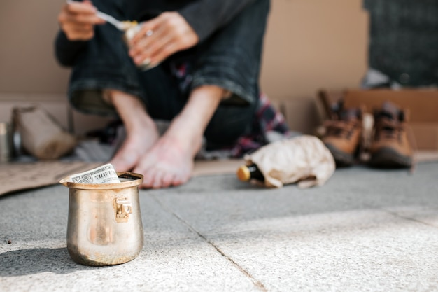 A picture of cup standing on concrete ground. there is a dollar in it. also we can see beggar's legs. he is holding a can with food in hands and spoon as well. there are lots of things lying on ground Premium Photo