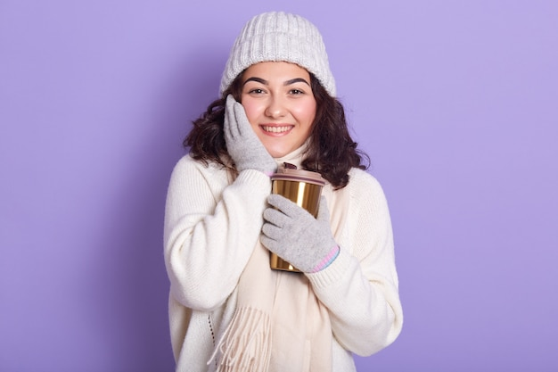 Picture of cute sweet young model touching her cheeck with hand, holding thermal mug in one hand Premium Photo