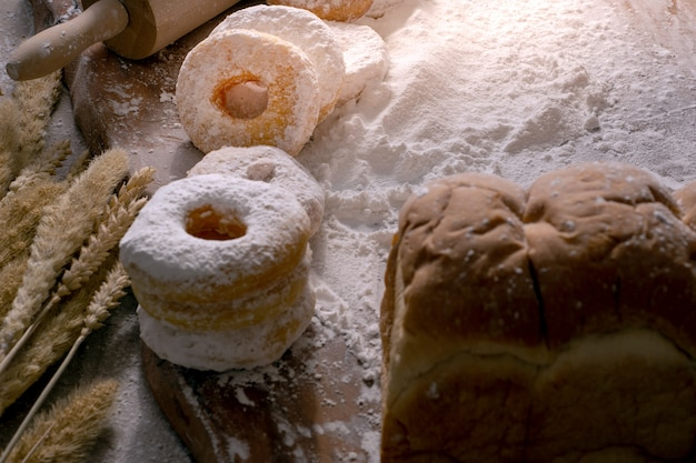 Picture of doughnuts with icing sugar on wooden table, food concept. Premium Photo