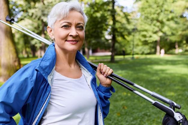Foto di signora europea fiduciosa alla moda con i capelli corti grigi in piedi nella pineta con bastoncini da nordic walking sulle spalle, tornando a casa dopo l'allenamento cardio, sorridendo ampiamente Foto Gratuite