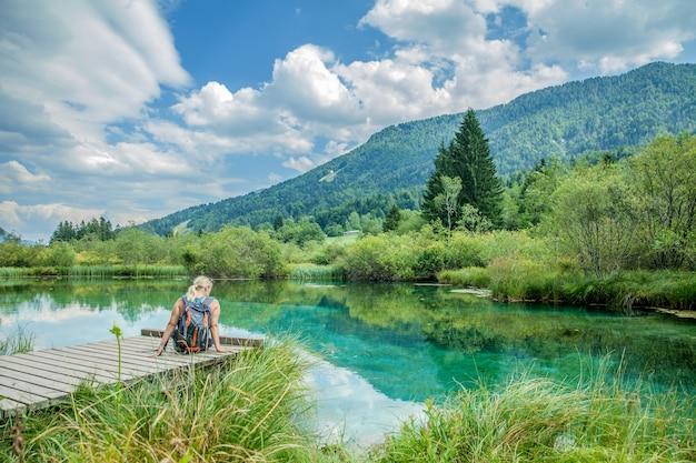 Immagine di una donna seduta su un ponte di legno contro un lago color smeraldo con una natura mozzafiato Foto Gratuite