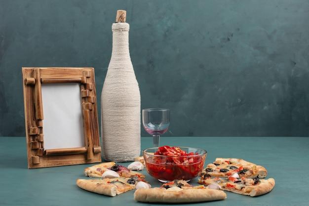 額縁、ボトル、ピクルスの赤唐辛子のボウル、青いテーブルの上のピザのスライス。 無料写真