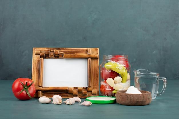 Рамка для картины, замаринованная в стеклянной банке, соль и свежие овощи на синем столе. Бесплатные Фотографии