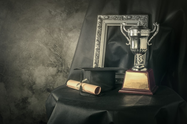 Picture frame, trophy cup and graduates still life photography success concept background. Premium Photo