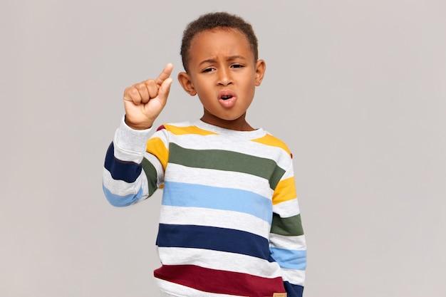 Immagine di divertente scolaro dalla pelle scura in elegante maglione a strisce con espressione facciale delusa, facendo il gesto con le dita come se tenesse qualcosa di molto piccolo. sconto, vendita e piccolo prezzo Foto Gratuite