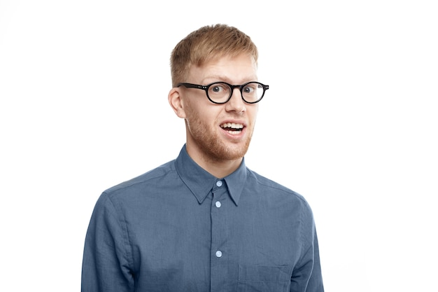 Picture of funny emotional young unshaven man wearing stylish glasses opening mouth in astonishment, being shocked with unexpected news, staring in full disbelief. shock and surprise Free Photo