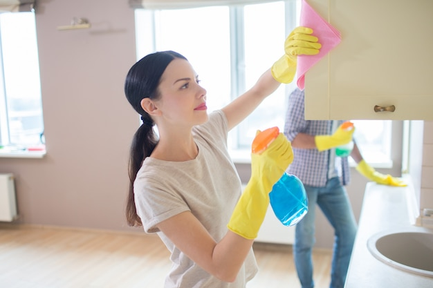 A picture of girl cleaning the surface of wardrobe with pink rag. her husband is standing and doing the same thing forward. people are concentrated. Premium Photo