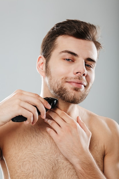 Picture of good-looking adult guy doing hygiene and health procedure with shaving his bristle using trimmer over grey wall Free Photo