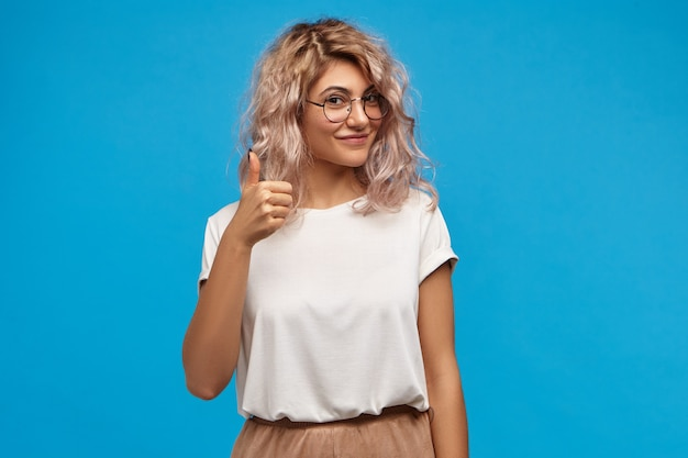 Picture of good looking friendly young caucasian female wearing stylish clothes and round eyeglasses making approval gesture, showing thumbs up sign at camera and smiling happily Free Photo
