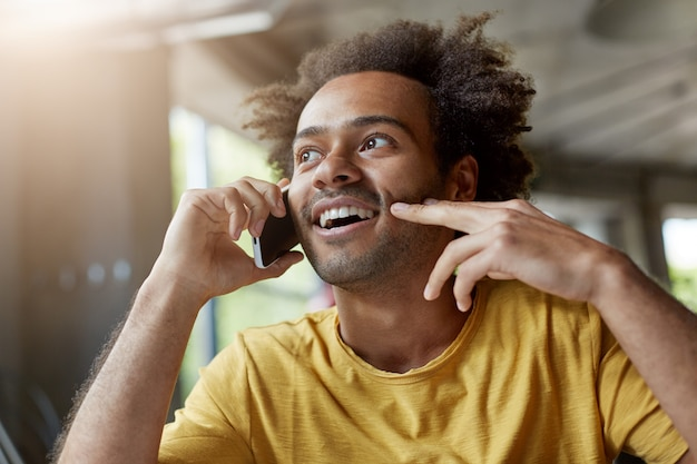 Picture of good-looking happy african man with beard and curly hair smiling cheerfully while talking on mobile phone, having interested look Free Photo