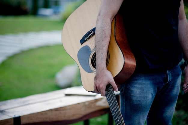 Picture of a guitarist, a young man playing a guitar while sitting in a natural garden Premium Photo