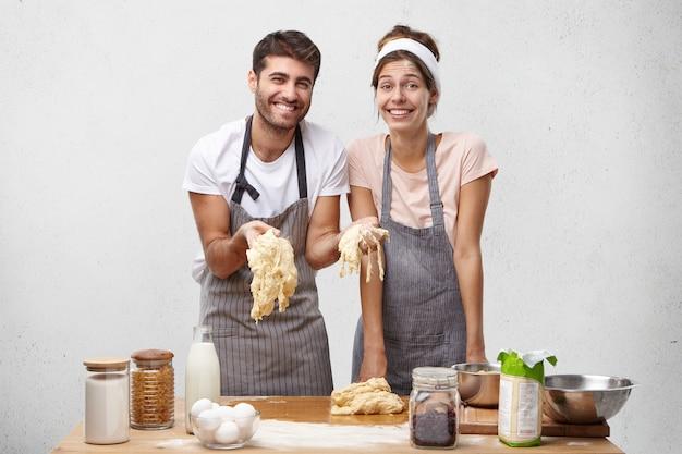 L'immagine della femmina e del maschio deliziosi felici prepara la pasta per cuocere il pane Foto Gratuite