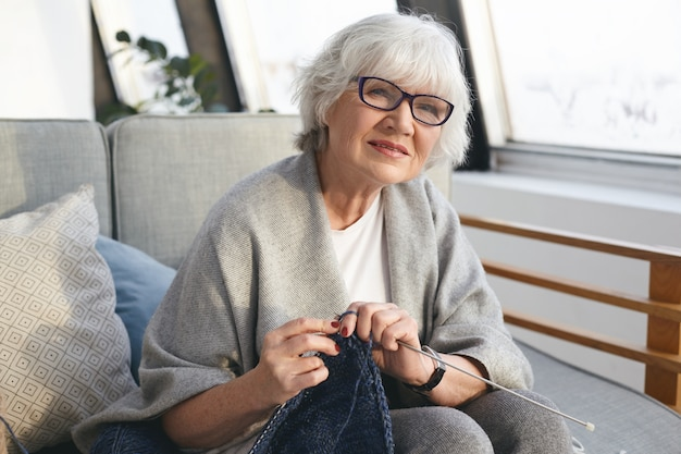 Picture of neat retired woman wearing wide scarf and eyeglasses knitting warm jumper for her daughter. attractive senior female knitter working from home, handmaking winter clothes for sale Free Photo