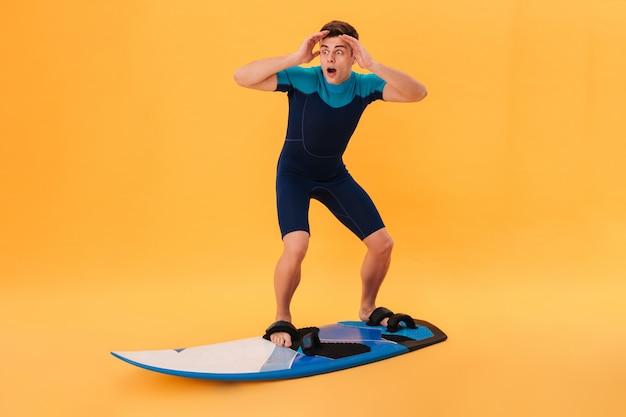 波のようにサーフボードを使用してウェットスーツのショックを受けたサーファーの写真 無料写真