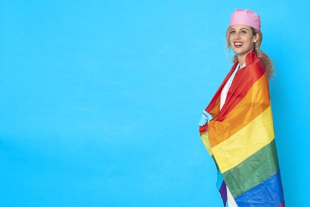 파란색 배경에 Lgbt 플래그와 함께 웃는 간호사의 그림 무료 사진