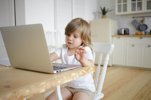 Изображение очаровательной милой девочки с пухлыми щеками, сидящей за столом на кухне, серфингом в интернете, просмотром мультфильмов, видеоблогом или играющими в онлайн-игры Бесплатные Фотографии