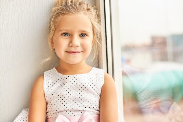 흥분된 행복한 미소로 아름다운 드레스를 입고 큰 파란 눈을 가진 사랑스러운 예쁜 유치원 소녀의 그림, 그녀의 생일 파티에서 친구를 찾고 창 옆에 앉아 무료 사진