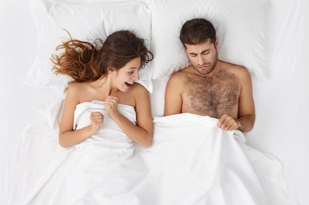 Изображение взрослого европейского бородатого мужчины и возбужденной женщины, лежащих в постели и подглядывающих под белым одеялом Бесплатные Фотографии