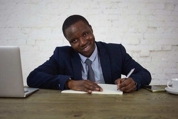 魅力的なアフリカの弁護士が彼のオフィスの机で働いて、日記にメモを書き、見て、笑っているスーツを着ている写真。コピーブックに彼のアイデアや計画を書き留めて幸せなビジネスマン 無料写真