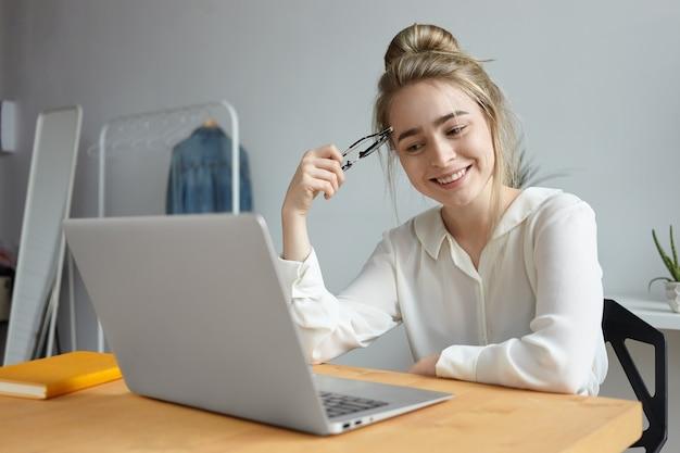 일반 휴대용 컴퓨터에서 인터넷을 서핑하는 머리 매듭을 가진 매력적인 쾌활한 학생 소녀의 그림, 집에서 테이블에 앉아 광범위하게 미소, 블로그 시청, 온라인 친구와 의사 소통 무료 사진