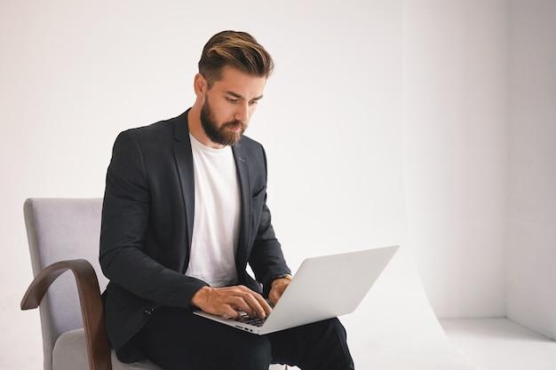 Фотография привлекательного успешного молодого европейского бородатого предпринимателя-мужчины, работающего удаленно, проверяющего электронную почту на портативном компьютере, с серьезным выражением лица и сосредоточенного на деловых вопросах. Бесплатные Фотографии