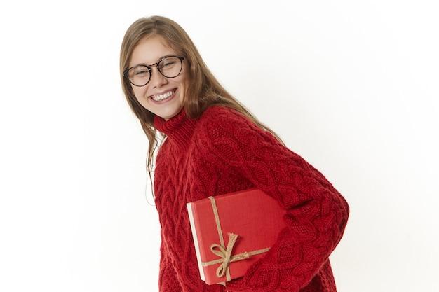 Изображение веселой привлекательной молодой девушки в очках и свитере с подарком в красной коробке и широко улыбающейся Бесплатные Фотографии