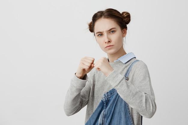 拳を握り締めて防御的な姿勢でカジュアルな立っている身に着けている集中している女性の写真。通りの泥棒に腹を立てて戦う準備ができて厳格な視線を持つフェミニンな女の子。ボディランゲージ 無料写真