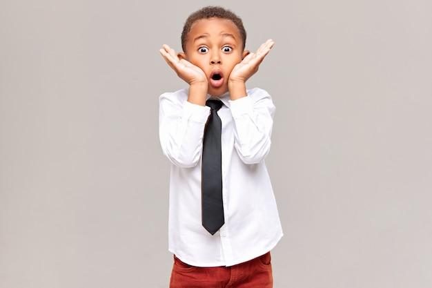 Фотография эмоционально забавного удивленного афроамериканского школьника в рубашке и галстуке, держащего руки у лица, широко открывающего глаза и шокированного удивительной неожиданной новостью. Бесплатные Фотографии
