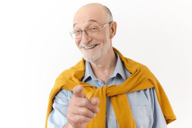 대머리 머리와 회색 수염을 가진 감정적 인 잘 생긴 수석 남자의 그림은 광범위하게 웃고 카메라에서 앞쪽 손가락을 가리키고, 재미있는 이야기 나 농담에 웃고, 흰색 스튜디오 벽에 고립 된 포즈 무료 사진