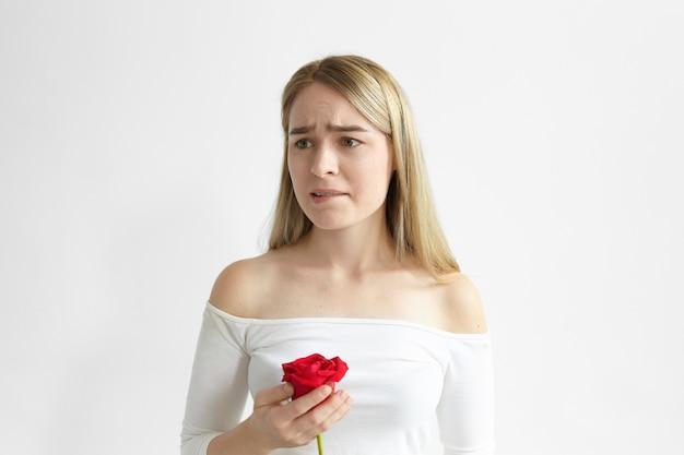彼女の恋人からの1つの赤いバラでポーズをとって、心配して動揺して、唇を噛んでいる欲求不満の美しい若い女性の写真 無料写真