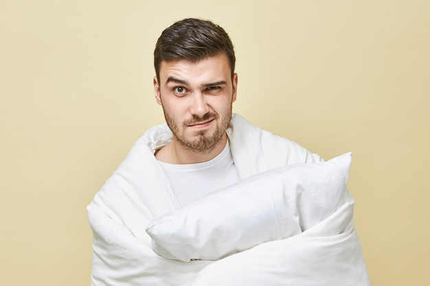 Фотография разочарованного молодого небритого мужчины, который чувствует себя напряженным, чтобы проснуться рано, завернутый в белое мягкое одеяло с подушкой в руках и сердитым выражением лица. постельные принадлежности Бесплатные Фотографии