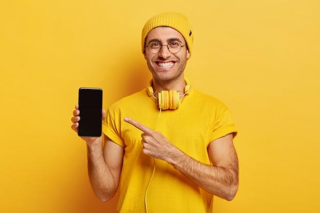 기쁜 잘 생긴 남자의 사진은 현대 가제트에서 스마트 폰, 포인트의 디스플레이를 보여줍니다 무료 사진