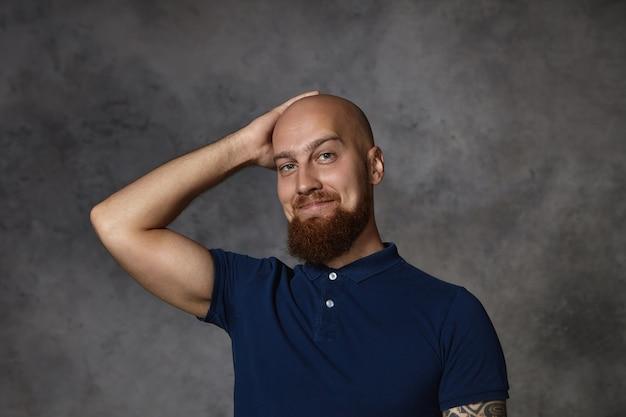 Изображение красивого привлекательного молодого бородатого мужчины в стильной рубашке поло с кокетливым выражением лица, почесывающего бритую лысину, стесняющегося во время разговора с красивой женщиной Бесплатные Фотографии