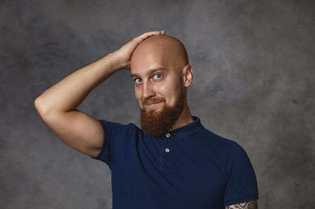 Изображение красивого симпатичного парня с густой бородой, застенчиво улыбающегося и держащего руку на своей бритой лысой голове, просящего милую женщину о свидании. портрет счастливого привлекательного бородатого парня, гордящегося своей прической Бесплатные Фотографии