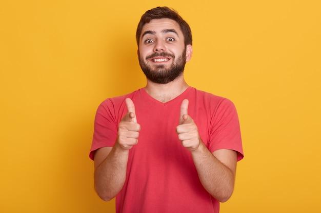 잘 생긴 웃는 현대인의 그림 두 엄지 손가락으로 확인 표시를 보여주는 빨간 캐주얼 T 셔츠, 모델 포즈 행복 한 표정으로 노란색, 수염 된 젊은 남성에 고립. 무료 사진