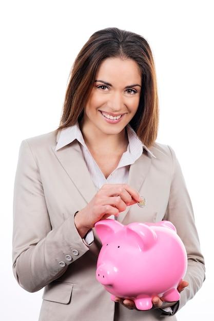 貯金箱とお金を持つ素敵な女性の写真 無料写真