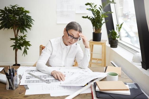 Фотография подчеркнутой расстроенной женщины-инженера среднего возраста в белой рубашке и очках, которая смотрит на чертежи или проектную документацию перед собой на столе, разочарованная, увидев так много ошибок Бесплатные Фотографии