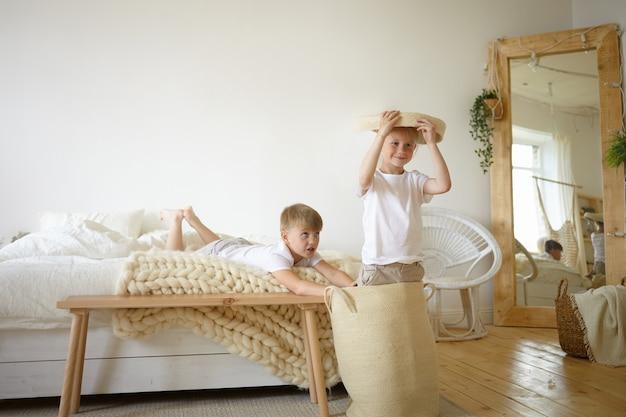 Представьте себе двух очаровательных кавказских школьников, которые веселятся в помещении, вместе играют в активные игры в родительской спальне, чувствуют себя счастливыми и беззаботными. симпатичные дети мужского пола, развлекая себя дома Бесплатные Фотографии