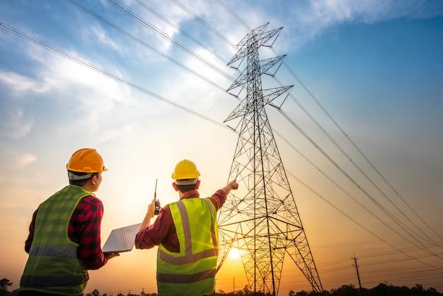 高圧電極での計画作業を確認するために、発電所に立っているコンピューターを使用して電気作業をチェックしている2人の電気技師の写真。 Premium写真