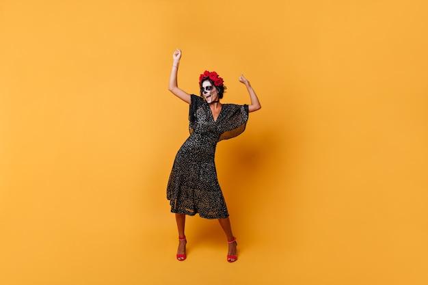 여자 즐겁게 비명과 오렌지 배경에 춤의 그림. 얼굴 아트가있는 폴카 도트 드레스의 소녀는 높은 정신으로 포즈를 취합니다. 무료 사진