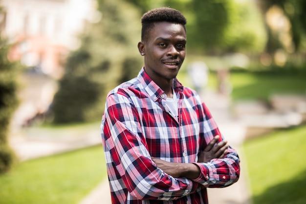 Изображение молодого африканского человека, идущего по улице, стоя со скрещенными руками. Бесплатные Фотографии