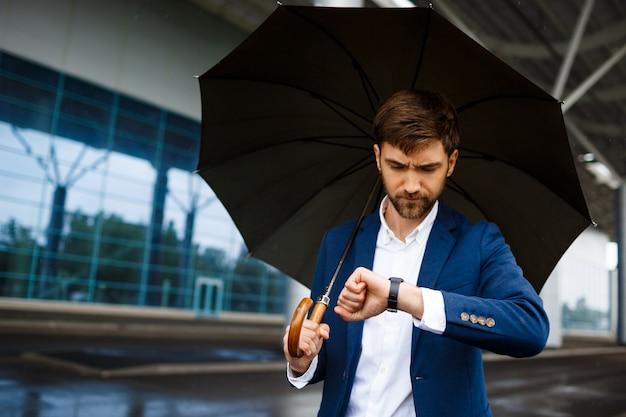Картина молодой бизнесмен, держа зонтик и глядя на часы в дождливый терминал Бесплатные Фотографии