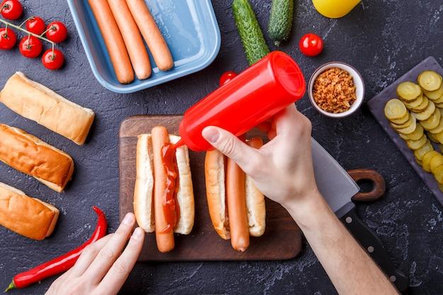 Картинка сверху стола с ингредиентами для хот-догов, разделочная доска, мужские руки Premium Фотографии